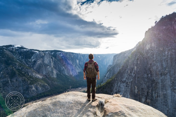 A young adult whit his backpack contemplating the view before him, at Yosemite National Park, California, USA.