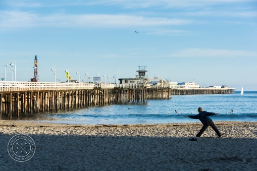 A man doing Yoga in the morning at the Santa Cruz Beach, with the pier in front of him, California, USA.